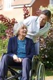 Cuidador que empuja a la mujer mayor en silla de ruedas fotografía de archivo libre de regalías
