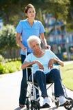 Cuidador que empuja a la mujer mayor infeliz en silla de ruedas Fotos de archivo libres de regalías