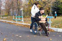 Cuidador que empuja a un hombre discapacitado en una silla de ruedas Imagen de archivo libre de regalías