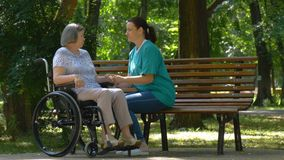 Cuidador que habla con la mujer mayor discapacitada en silla de ruedas al aire libre almacen de metraje de vídeo
