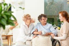 Cuidador que habla con una mujer mayor sonriente y su amigo en th fotografía de archivo