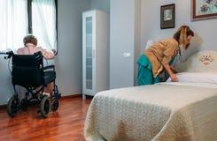 Cuidador que hace la cama de un paciente mayor Imágenes de archivo libres de regalías