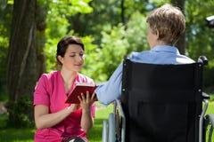 Cuidador que lee un libro a la mujer discapacitada Foto de archivo
