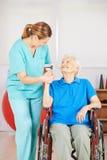 Cuidador que lleva a cabo la mano de la mujer mayor Imagen de archivo