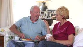 Cuidador que se sienta con el hombre mayor mientras que él come el almuerzo almacen de video