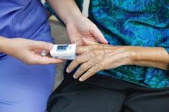 Cuidador que supervisa la saturación del oxígeno en la yema del dedo de ancianos fotos de archivo