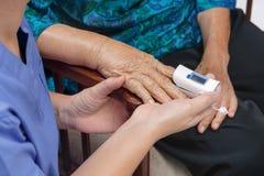 Cuidador que supervisa la saturación del oxígeno en la yema del dedo de la mujer mayor fotos de archivo