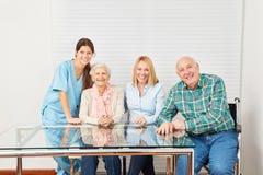 Cuidador y familia feliz en casa de retiro Imágenes de archivo libres de regalías