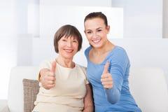 Cuidador y mujer mayor que muestran los pulgares para arriba Foto de archivo