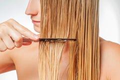 Cuidados capilares A mulher bonita está escovando seu cabelo louro molhado fotos de stock