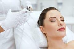 Cuidados com a pele da cara da beleza Mulher que obtém o tratamento do pulverizador do oxigênio foto de stock