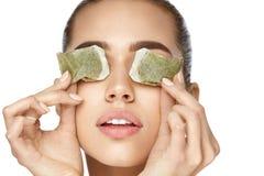 Cuidados com a pele do olho Mulher bonita com o saquinho de chá verde sob os olhos fotografia de stock