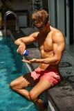 Cuidados com a pele do verão Homem que aplica-se bronzeando-se a associação próxima de creme de Sun fotos de stock