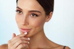Cuidados com a pele dos bordos Mulher com a cara da beleza que aplica o bálsamo de bordo sobre imagens de stock