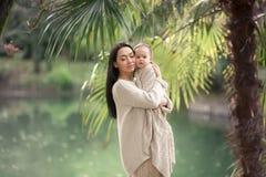 Cuidados jovenes y felices de la madre para su hijo joven, y los paseos a lo largo de la orilla del lago en el verano en el parqu fotografía de archivo