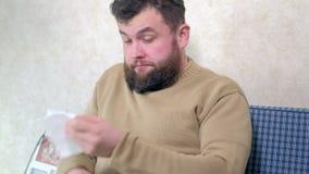 Cuidados médicos, gripe, higiene e conceito dos povos - nariz de sopro doente do homem ao guardanapo de papel em casa filme