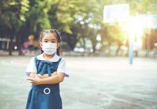 Cuidados médicos - menina que veste uma máscara protetora Fotografia de Stock Royalty Free