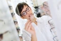 Cuidados médicos, visão e conceito da visão - mulher feliz que escolhe vidros na loja do sistema ótico imagens de stock