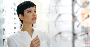 Cuidados médicos, visão e conceito da visão - mulher feliz que escolhe vidros na loja do sistema ótico foto de stock royalty free