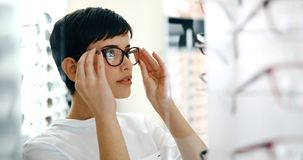 Cuidados médicos, visão e conceito da visão - mulher feliz que escolhe vidros na loja do sistema ótico fotos de stock