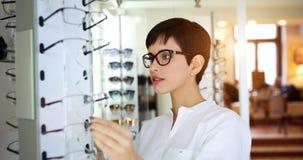 Cuidados médicos, visão e conceito da visão - mulher feliz que escolhe vidros na loja do sistema ótico imagem de stock