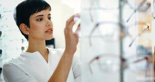 Cuidados médicos, visão e conceito da visão - mulher feliz que escolhe vidros na loja do sistema ótico imagem de stock royalty free