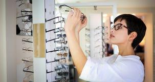 Cuidados médicos, visão e conceito da visão - mulher feliz que escolhe vidros na loja do sistema ótico fotografia de stock