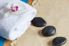 Cuidar terapia en exceso en la playa con masaje de piedra caliente Fotos de archivo