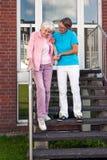 Cuide al ayudante que ayuda a una señora mayor en pasos Foto de archivo libre de regalías