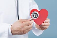 Cuide al cardiólogo que lleva a cabo un corazón rojo en sus manos y estetoscopio Cardiología y concepto de la enfermedad cardíaca fotografía de archivo libre de regalías