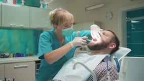 Cuide al dentista que hace una inyección del anestésico local en las gomas almacen de video