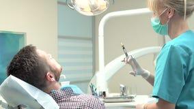 Cuide al dentista que hace una inyección del anestésico local en las gomas resbalador almacen de metraje de vídeo