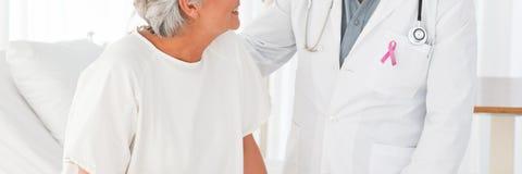 Cuide al hombre con la cinta de la conciencia del cáncer de pecho con el paciente fotos de archivo