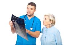 Cuide al hombre que muestra MRI a su paciente mayor Imagenes de archivo