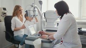 Cuide al optometrista en clínica que comprueba la visión del ` s de la niña - oftalmología del ` s de los niños imagen de archivo