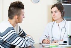Cuide al paciente adolescente de recepción y que pregunta en la oficina Imagenes de archivo