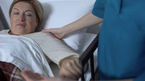 Cuide al paciente maduro débil de ayuda de la señora para levantarse el lecho de enfermo, yendo a los procedimientos almacen de video