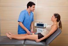 Cuide al terapeuta que comprueba el electrostimulation del músculo a la mujer Imagen de archivo