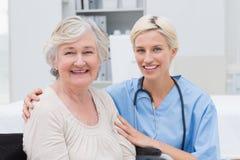 Cuide con el brazo alrededor de paciente mayor en clínica Fotografía de archivo libre de regalías