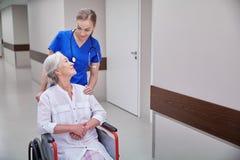 Cuide con la mujer mayor en silla de ruedas en el hospital Fotografía de archivo libre de regalías
