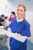 Cuide con los brazos doblados con el paciente y el dentista detrás de ella Imagen de archivo libre de regalías