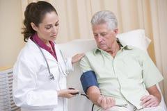 Cuide controlar la presión arterial del hombre en sitio del examen Imagenes de archivo