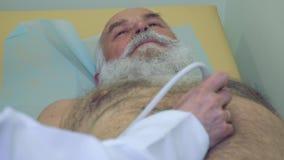 Cuide el abdomen de examen del hombre mayor con el equipo de la sonografía almacen de video