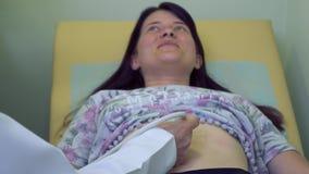 Cuide el abdomen del ` s de la mujer del control con el equipo del ultrasonido metrajes