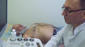 Cuide el control el abdomen del equipo de la sonografía del wuth del hombre mayor almacen de video