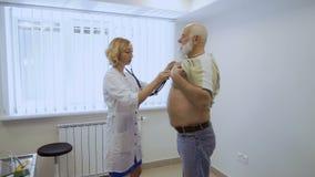 Cuide el control el corazón del hombre mayor con el estetoscopio almacen de video