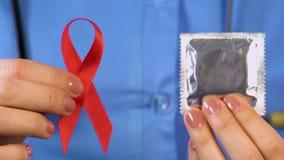 Cuide el donante de los condones de la gente y de las cintas rojas campaña social contra el VIH y LO AYUDA almacen de metraje de vídeo