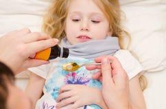 Cuide el donante de una cuchara del jarabe a la niña Foto de archivo libre de regalías
