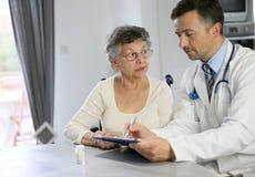 Cuide el donante de una prescripción médica a una mujer mayor Foto de archivo libre de regalías