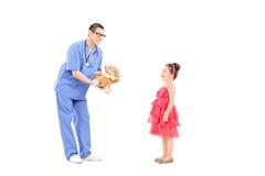 Cuide el donante del oso de peluche a una niña sorprendida Fotos de archivo